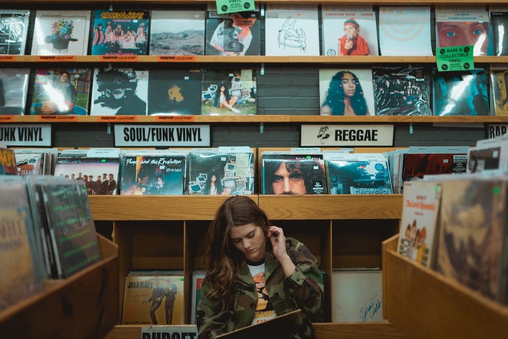 woman in green jacket standing beside books