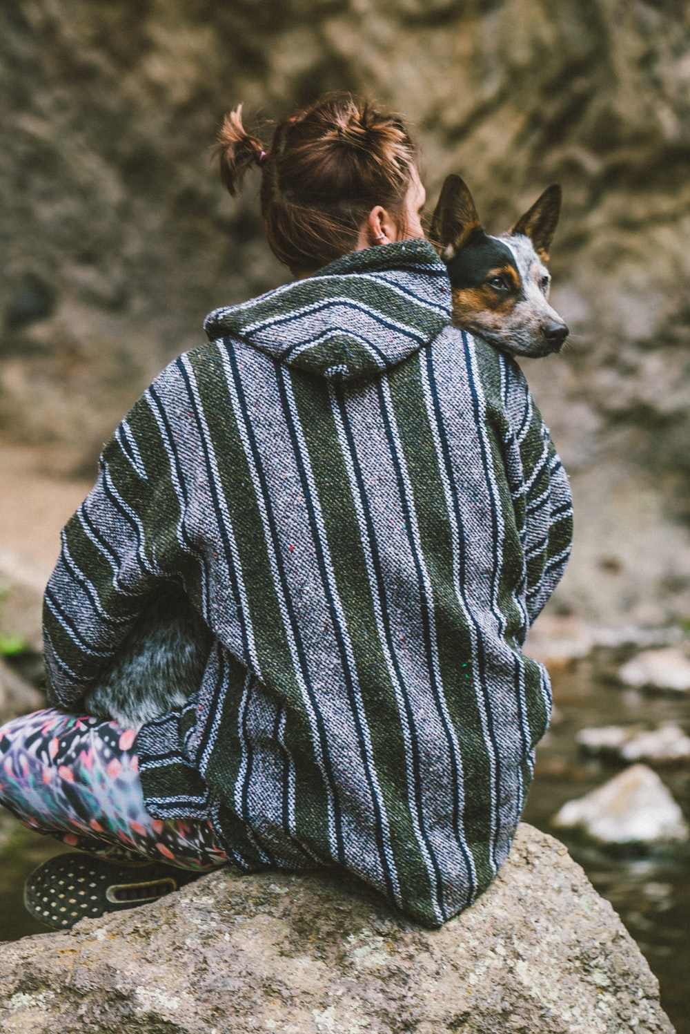woman in black and white striped sweater holding black and white short coat small dog