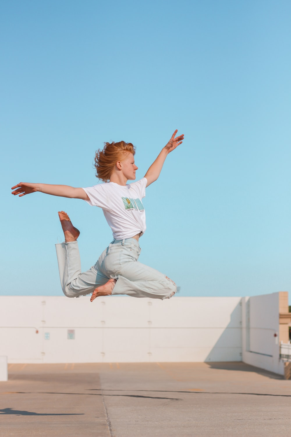 woman in white t-shirt and white pants jumping