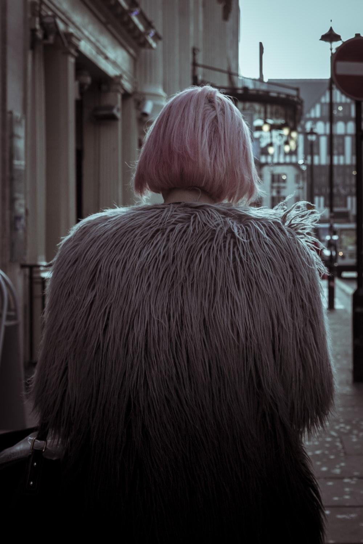 woman in brown fur coat standing on sidewalk during daytime