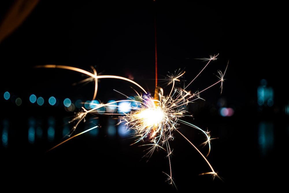 white and yellow fireworks in dark night sky