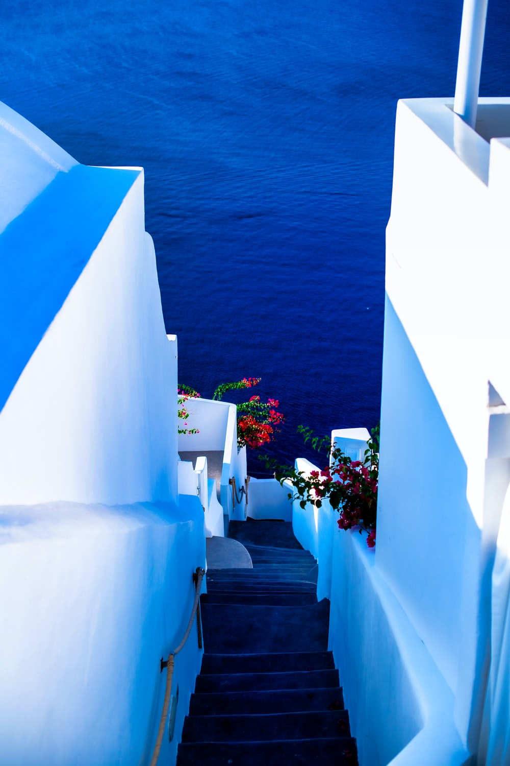 white concrete staircase near body of water during daytime