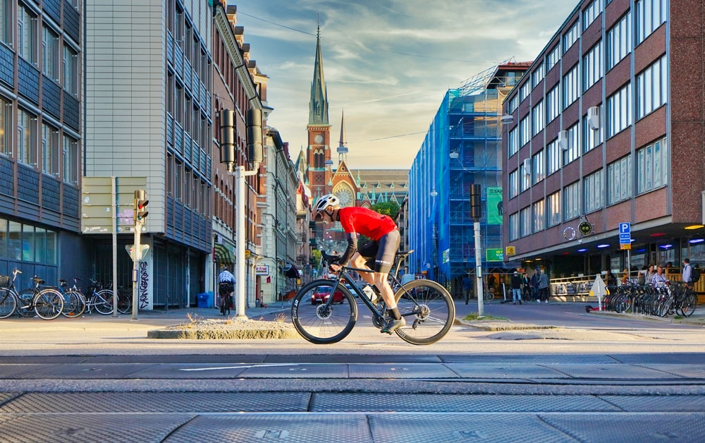 man in red shirt riding bicycle on road during daytime