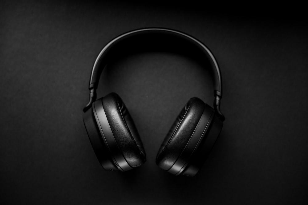 black wireless headphones on black surface