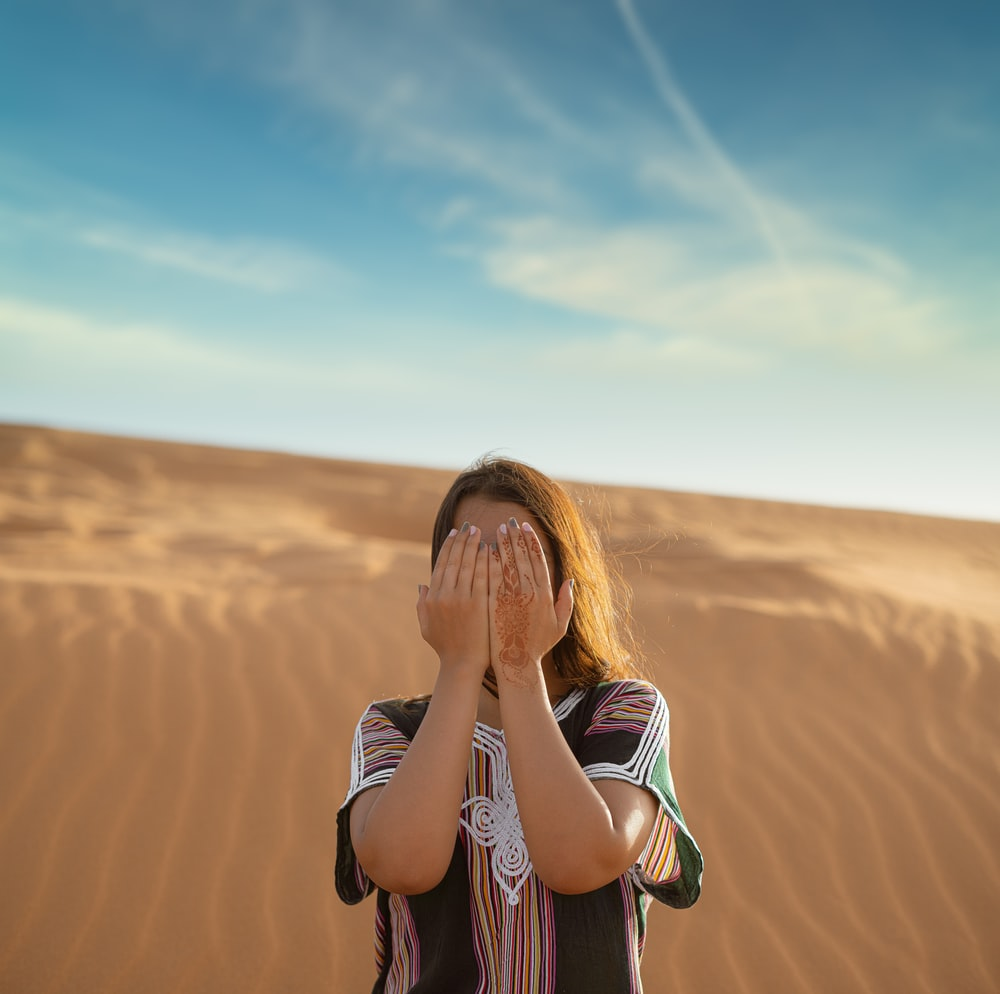 woman in black and white stripe long sleeve shirt standing on brown sand during daytime