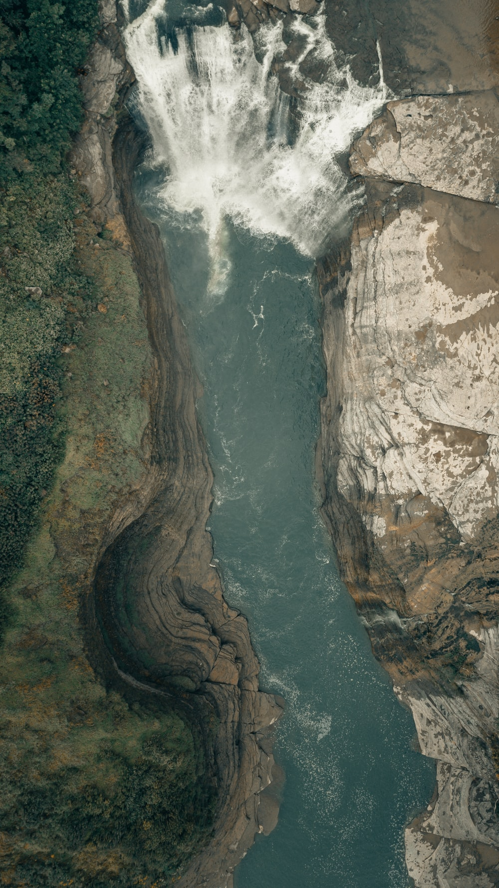 water falls between brown rocky mountain during daytime