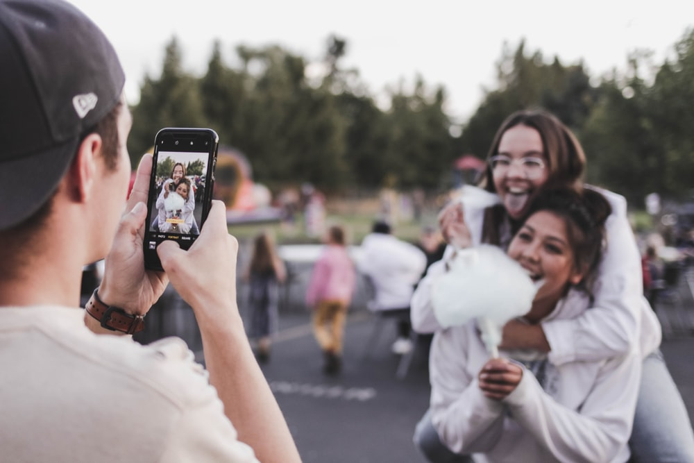 woman in white dress holding black smartphone