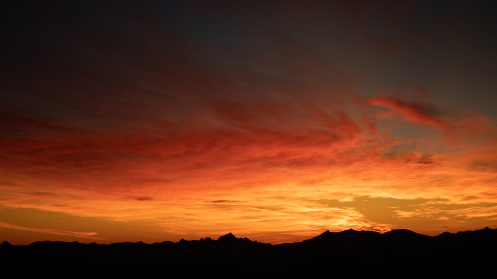 silhouette of mountain under orange and blue sky