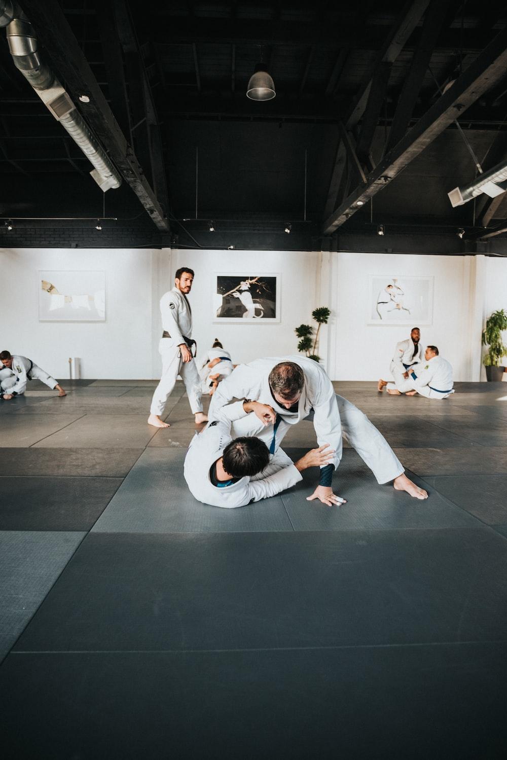 man in white long sleeve shirt and black pants sitting on black floor