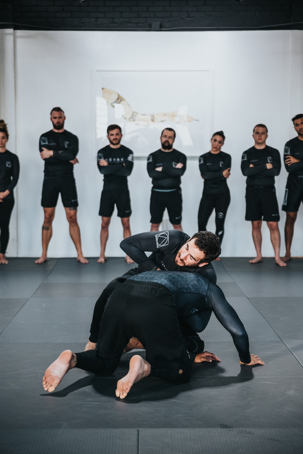 group of people in black shirts and black pants doing yoga
