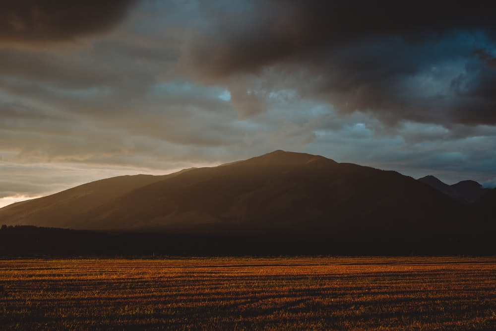brown field near mountain under cloudy sky during daytime