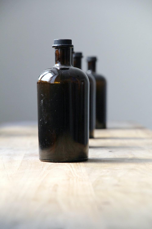 black glass bottle on white textile