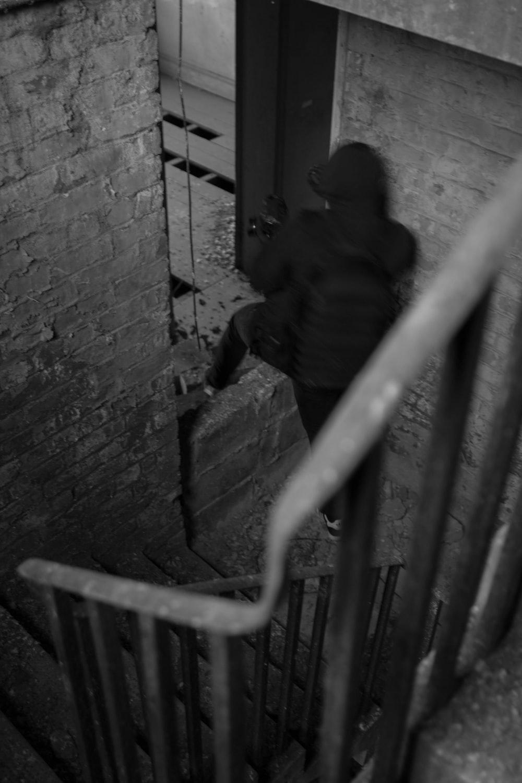man in black jacket standing beside metal fence