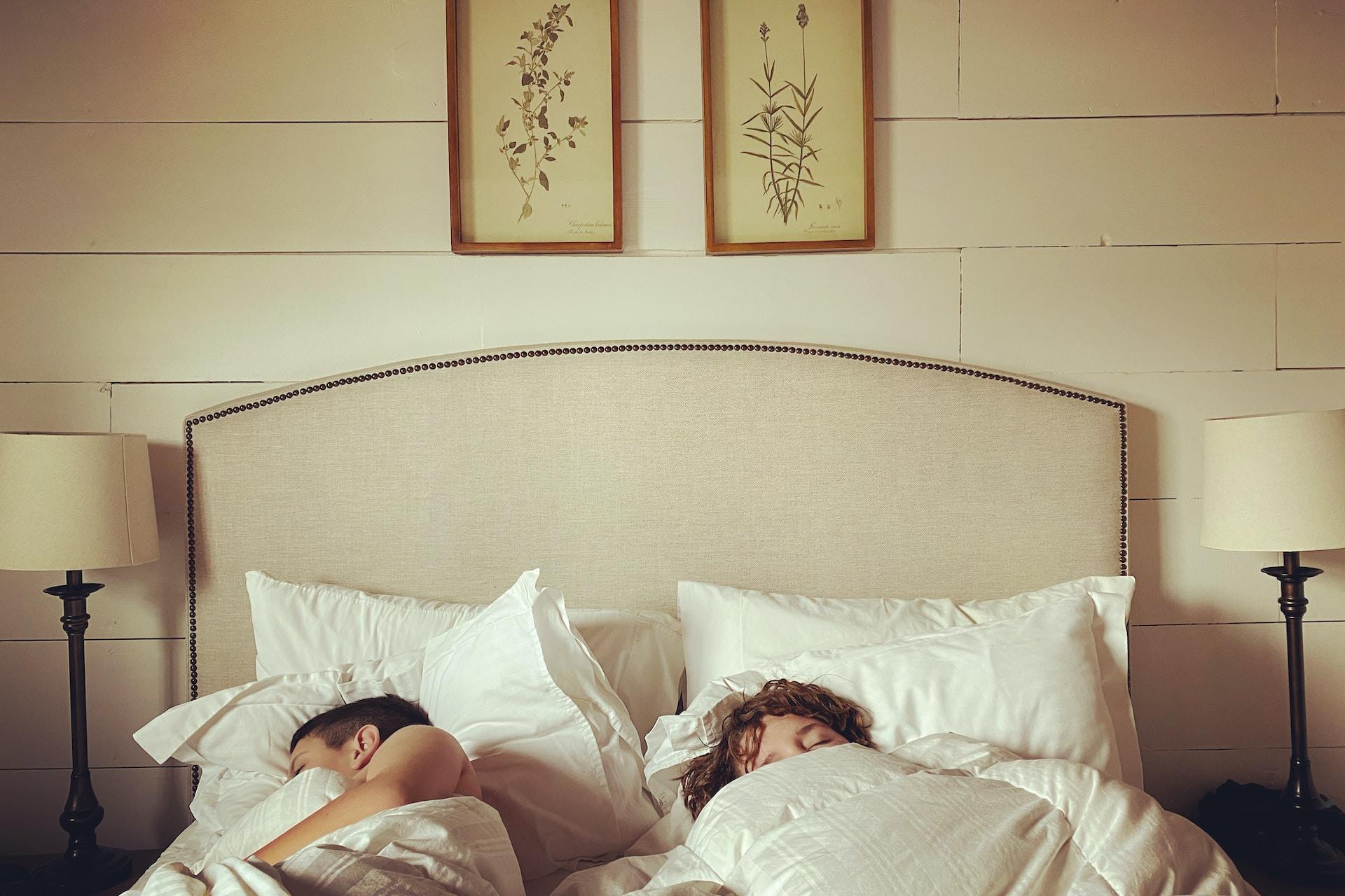 2 children lying on bed
