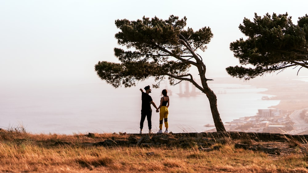 man and woman standing on brown grass field near green tree during daytime