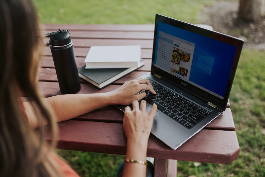 person using macbook pro on brown wooden table during daytime