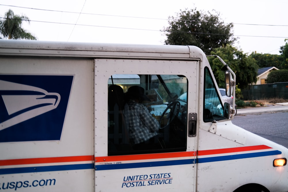 white and blue van near green tree during daytime