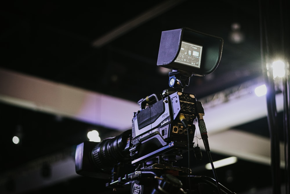 black video camera on black tripod