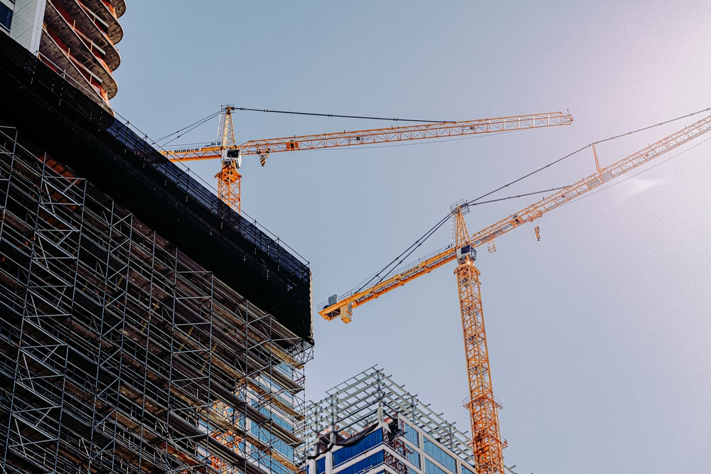 yellow crane near building during daytime