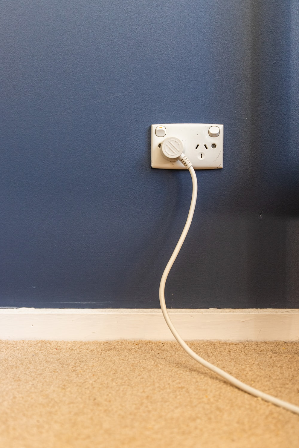 white electric plug on blue wall