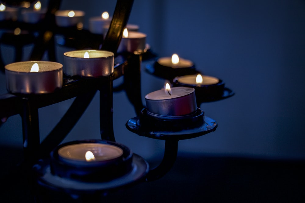 lighted candles on black metal candle holder