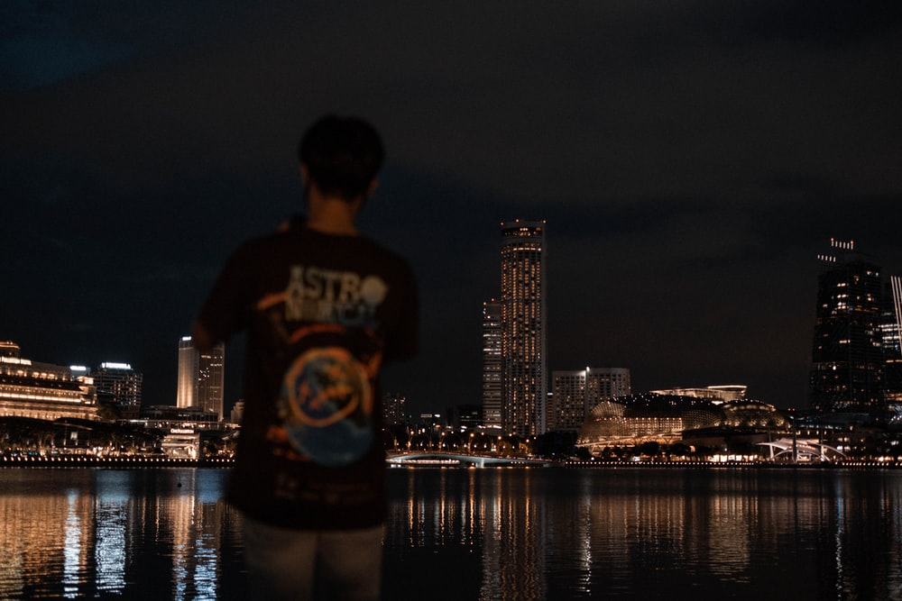 man in white and black crew neck t-shirt standing near body of water during night