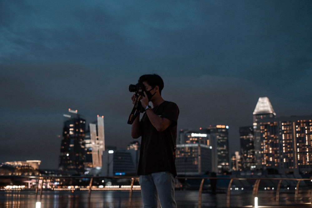 man in black shirt and blue denim jeans holding camera standing on the ground during night