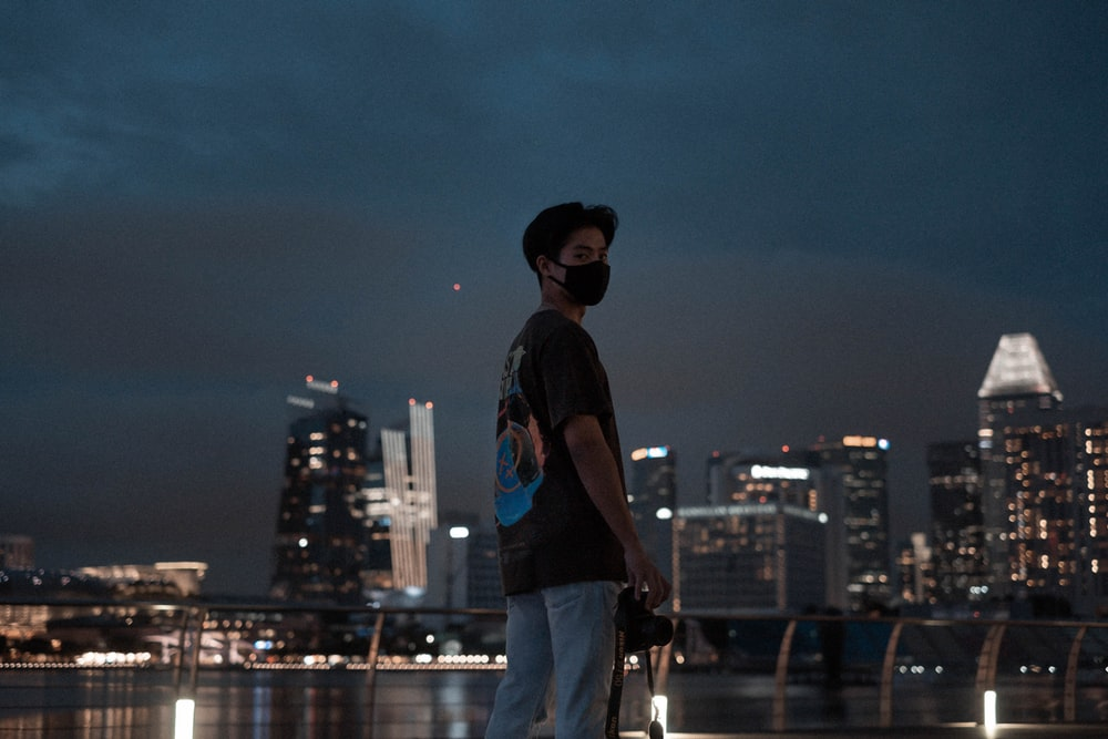 man in black t-shirt and blue denim jeans standing on rock looking at city buildings