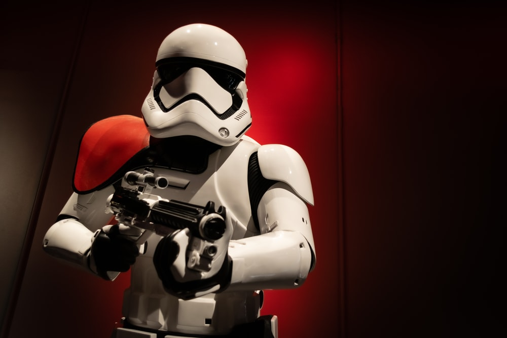 white and black robot holding gun