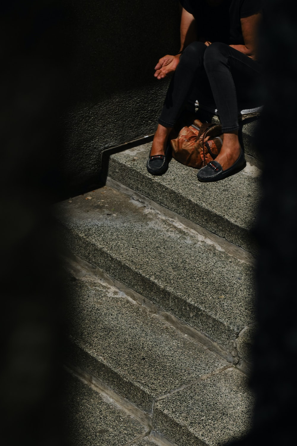 person in black pants and brown leather shoes standing on gray concrete stairs