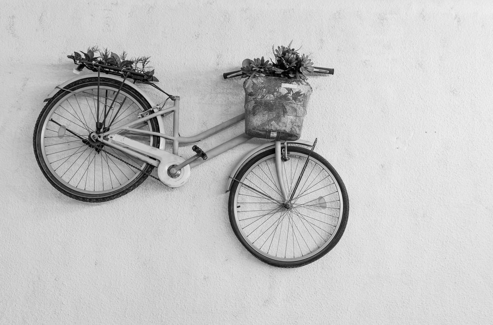 black bicycle with basket on white wall