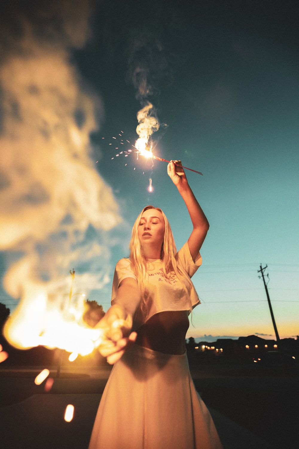 woman in white crop top holding sparkler