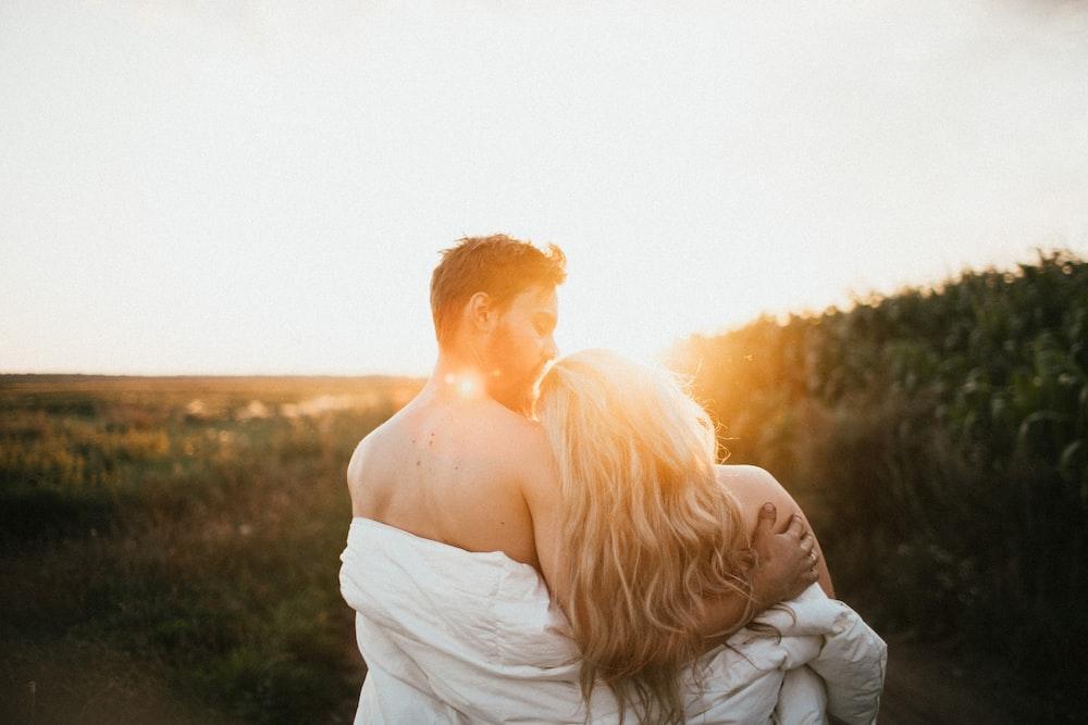 woman in white dress hugging man in gray dress shirt