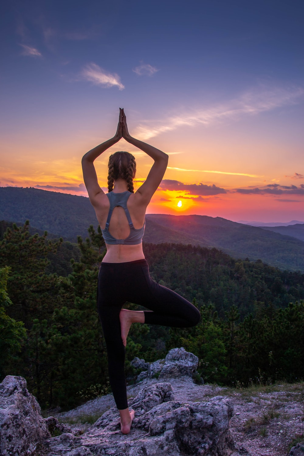 woman in black leggings standing on rock formation during sunset
