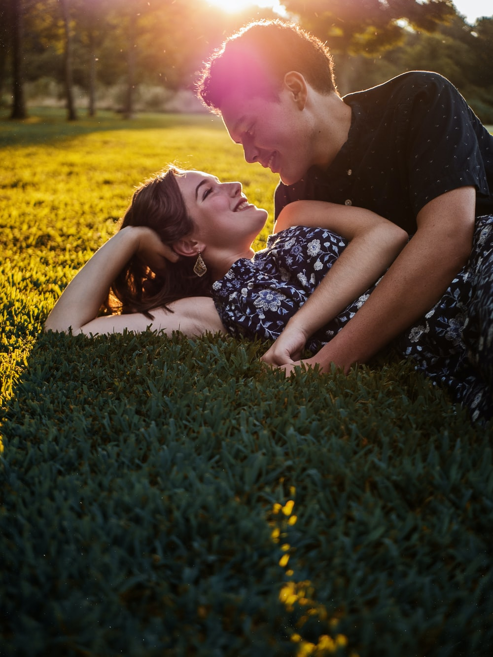 man and woman lying on green grass field during daytime