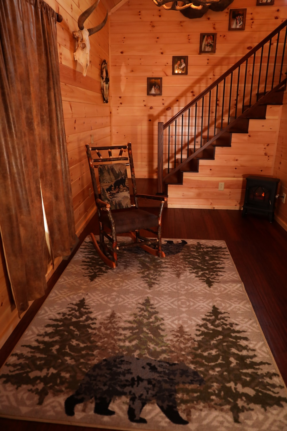 brown wooden chair on brown and white floral area rug