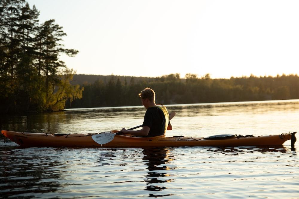 woman in yellow shirt riding on brown kayak on lake during daytime