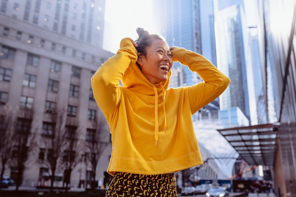 woman in yellow long sleeve shirt standing on building during daytime
