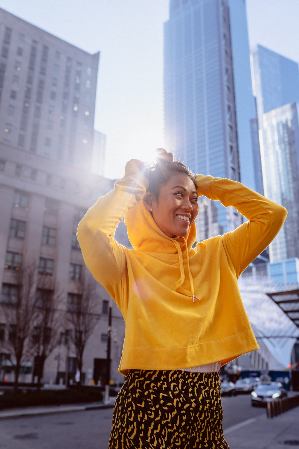 woman in yellow hoodie standing on the city during daytime