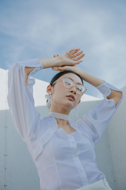woman in white long sleeve shirt wearing black sunglasses
