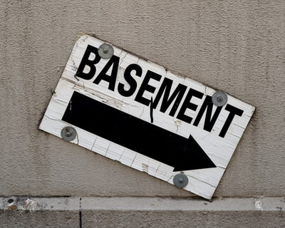 A concrete wall with a sign reads basement and an arrow that points down in black letters on white background.