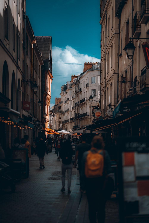 people walking on street between buildings during night time