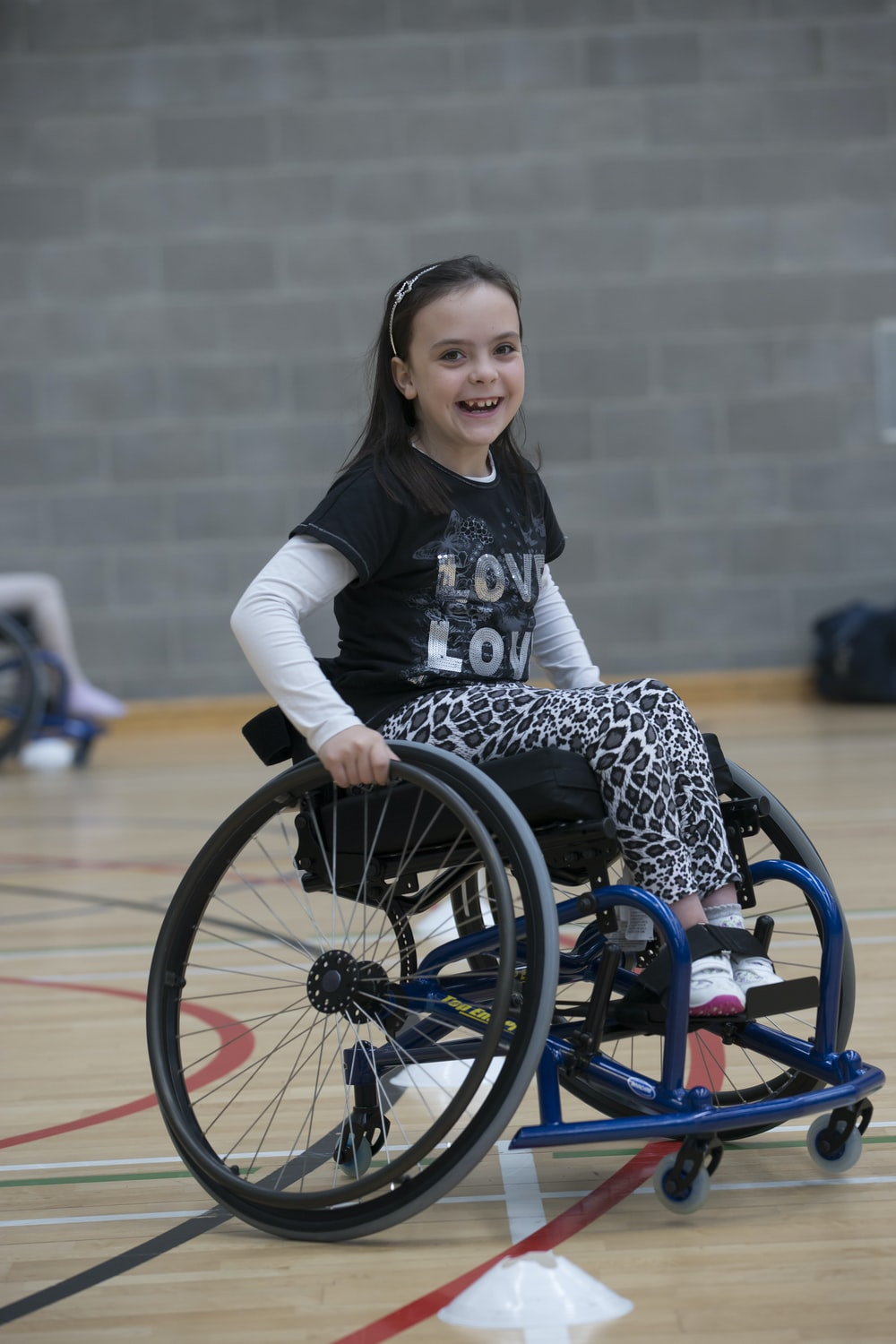 girl in black and white long sleeve shirt sitting on black wheelchair