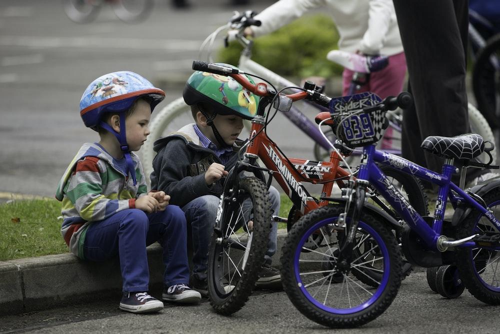 children riding on red mountain bike during daytime
