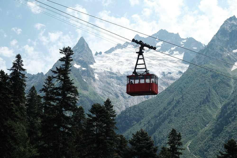 red cable car over green pine trees during daytime