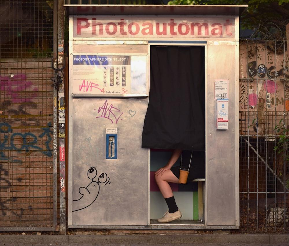 woman in black dress standing on brown brick floor