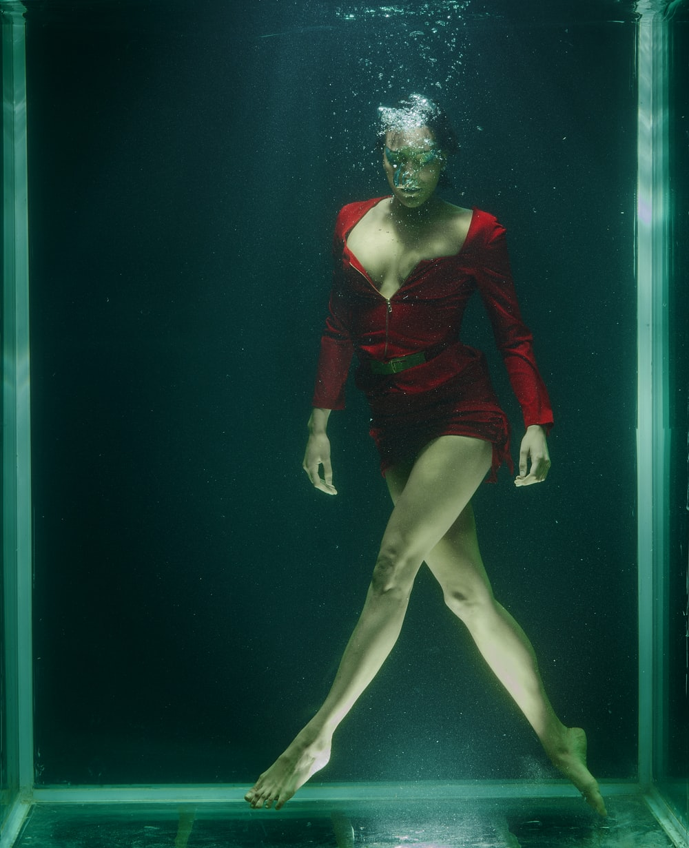 woman in red long sleeve shirt and black panty under water