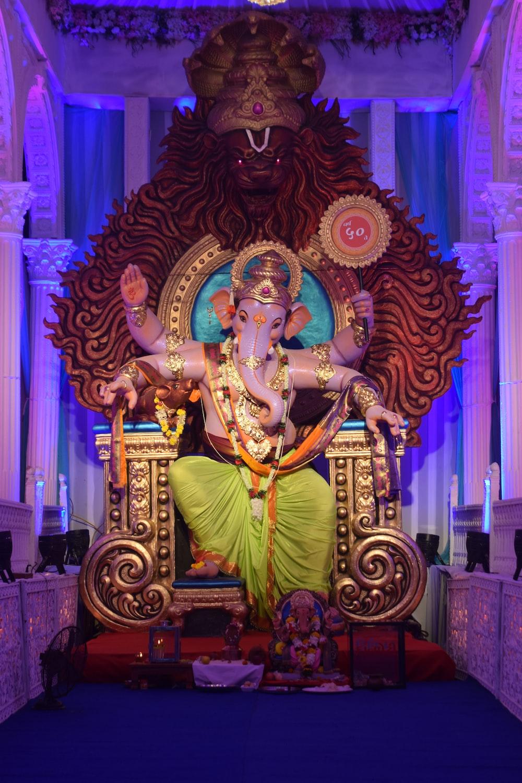 gold hindu deity figurine on brown wooden table