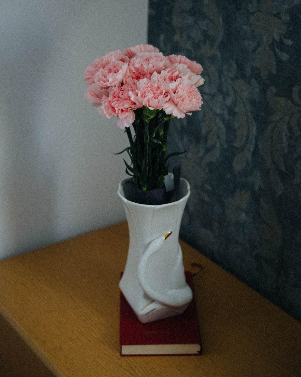 pink and white flower in white ceramic vase