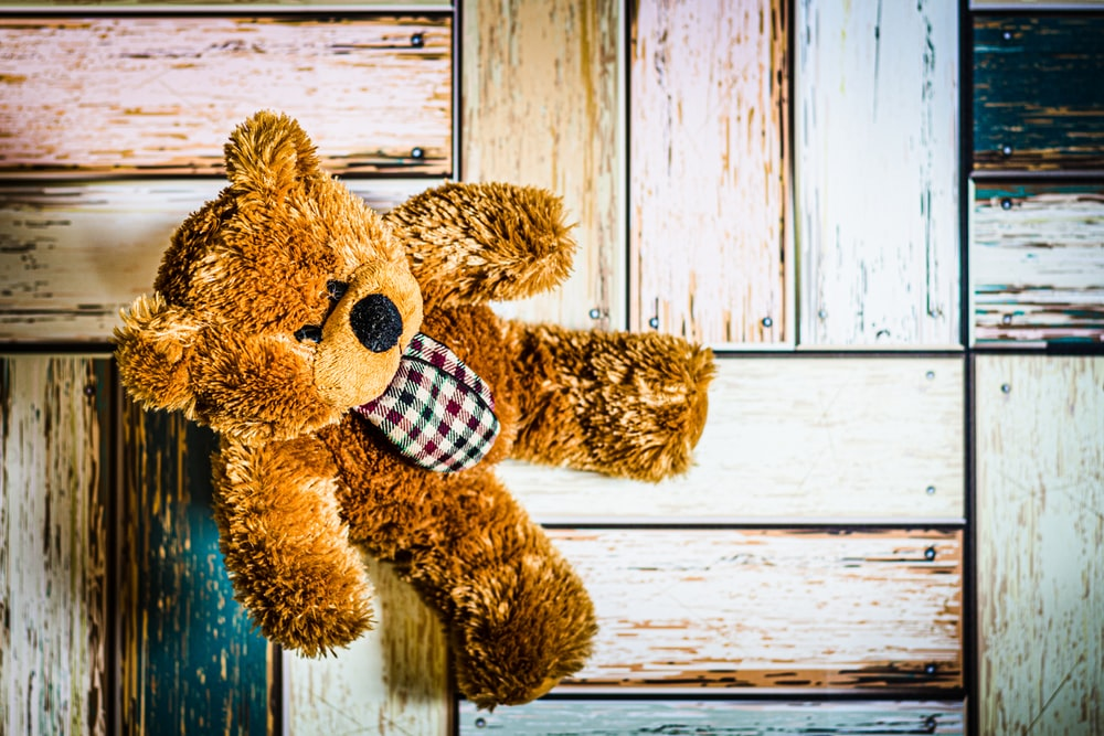 brown teddy bear on white wooden plank